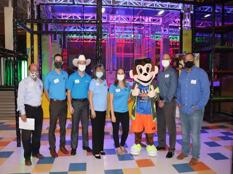 Pictured from left to right: Steve Spratt (FGUA System Manager), Matthew Rihs (FGUA), Austin Groover (Urban Air Adventure Park), Patti Clark (FGUA), Caytee Hollingsworth (FGUA), Urby (Urban Air Adventure Park Mascot), Michael Carballa, P.E., (Pasco County Assistant County Administrator, Public Infrastructure), and Mike Wells (Pasco County Commissioner)